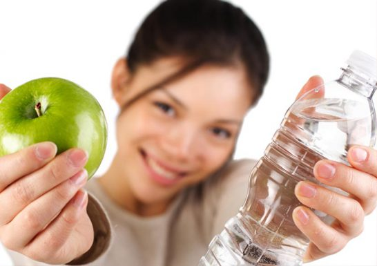Woman with apple and water for weightloss