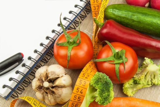 Fruit, vegetables, tape measure and note pad for weight loss